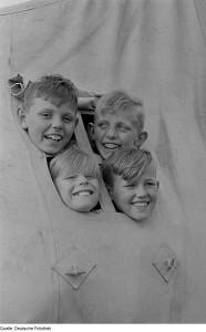 Vier Jungen aus dem Zeltfenster schauend. Foto: Renate Rössig, Roger Rössig, Deutsche Fotothek, CC-BY-SA-3.0